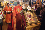 Christmas Eve Vigil Service, St. Sava Serbian Orthodox Church, Jackson, Calif...Reader Dan Stojanovich with a vessel of bread for blessing by Fr. Steve Tumbas...In the foreground (the center of the church) is placed an icon of Mary, Mother of God (Theotokos), with baby Jesus Christ at his birth.