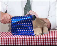 BNPS.co.uk (01202 558833)<br /> Pic: PeterWillows/BNPS<br /> <br /> Takes seconds...<br /> <br /> The answer to every males gift wrapping nightmares - Man Wrap.<br /> <br /> An easy-to-use type of wrapping paper has been invented just for men in a bid to get them to start presenting neatly covered gifts.<br /> <br /> The blue, star patterned gift-wrap can be used without scissors or sellotape and can cover an item in seconds.<br /> <br /> Users simply have to roll out the paper and place their gift in the centre, tear off a strip and then twist it around the present to secure it in place.<br /> <br /> It was created by designer Martin Grix who was shocked at the sheer amount of men he heard found the wrapping process difficult and were even resorting to using bin liners.<br /> <br /> He came up with the unique roll of paper, 'Man Wrap', as a solution in the hope that it would encourage men to start covering their gifts.<br /> <br /> The tube of decorative paper provides 16ft of gift-wrap with a width of 8ins to coat small presents such as boxes and bottles.<br /> <br /> It costs 4.99 pounds from www.themonsterfactory.com