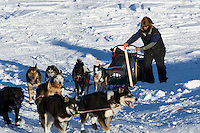 Sonny Lindner runs up the bank of the Yukon River and into the Kaltag checkpoint on Saturday during Iditarod 2011