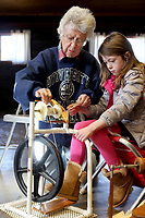 NWA Democrat-Gazette/DAVID GOTTSCHALK Caye Mott (left) works with her granddaughter Piper Mott, 7, on a spinning wheel Wednesday, January 3, 2018, during a Spin-A-Round meeting of the Wool and Wheel Handspinners in the Latta Barn at Prairie Grove Battlefield State Park. The group meets every first Wednesday of the month at the park and every third Saturday at Ozark Folkways in Winslow. The group is open to the public and invites participation and observation.