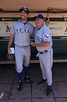 OAKLAND, CA - AUGUST 3:  Adam Rosales #9 and coach Jackie Moore #4 of the Texas Rangers pose for a picture in the dugout before the game against the Oakland Athletics at O.co Coliseum on Saturday, August 3, 2013 in Oakland, California. Photo by Brad Mangin