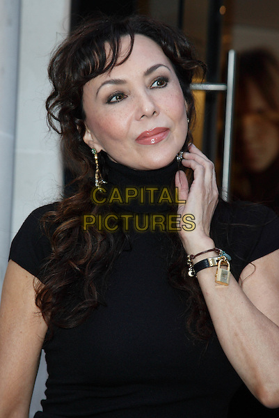 MARIE HELVIN.Vogue 'Fashion's Night Out ' launch at Burberry's store in New Oxford Street, London, England..September 10th 2009.half length high collar top hand gold lock locket bracelet jewellery jewelry dangling earring black.CAP/ROS.©Steve Ross/Capital Pictures.