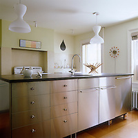 Behind the kitchen island, made out of Ikea stainless steel-fronted cabinets, is the original cooker and the wall clock is by George Nelson