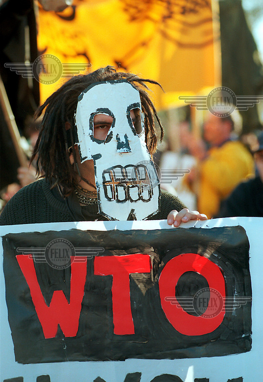 A protester against the World Trade Organisation (WTO) conference takes part in a procession in Seattle's Capitol Hill district in the run up to the Millennium Round talks on global trade. Seattle was a landmark protest for anti-globalisation campaigners.