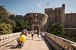 Walled city (stari grad) of Duvbrovnik, founded c. 972 along the Dalmatian Coast on the Adriatic Sea in Croatia--crossing the bridge to the entrance