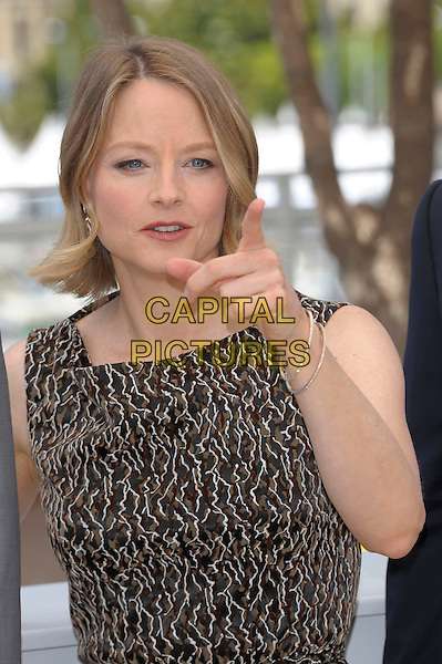 JODIE FOSTER.'The Beaver' photocall at the Palais des Festival, 64th International Cannes Film Festival, France.17th May 2011.half length dress sleeveless brown beige print hand finger pointing  .CAP/PL.©Phil Loftus/Capital Pictures.