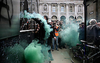 A demonstrator throws a smoke bomb through the smashed window of the Royal Bank of Scotland (RBS) as thousands of protestors descended on the City of London ahead of the G20 summit of world leaders to express anger at the economic crisis, which many blame on the excesses of capitalism. RBS was the focus of anger because it had to be bailed out by the government.