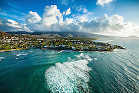 An aerial shot of a big wave rushing towards Black Point on O'ahu, with Koko Crater in the distance.