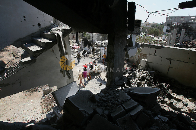 Palestinians inspect the rubble of destroyed houses  in Khan Younis in the southern Gaza Strip on July 26, 2014. Palestinians retrieved dozens of bodies from the rubble of Gaza homes during a brief truce in the fighting, raising to over 900 the overall death toll of Israel's onslaught on the territory since July 8, medics said. Photo by Eyad Al Baba
