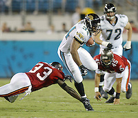 Jacksonville Jaguar running back Stacey Mack (#34) eludes a pair of Tampa bay Buccaneer defenders during an NFL preseason game in Jacksonville, FL on Friday, August 15, 2002.  Tampa bay won the game 20 to 0. (Photo by Brian Cleary/ www.bcpix.com )