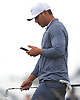 Brooks Koepka checks his mobile phone as he walks on the 17th Hole during a practice round prior to the U.S. Open Championship at Shinnecock Hills Golf Club in Southampton on Wednesday, June 13, 2018.