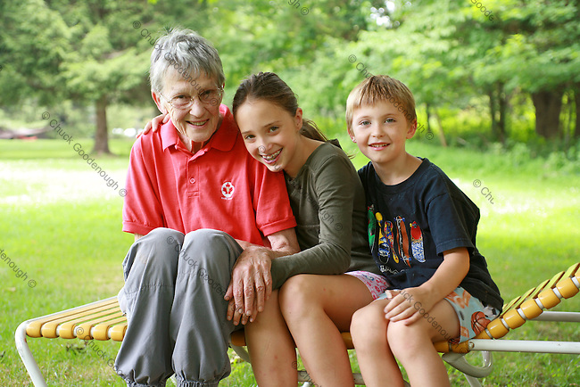 Stock Photo of Grandchildren giving Grammie and hug out on the back lawn at Grandma's House