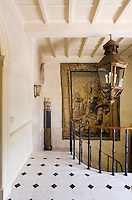 An impressive tapestry hangs on the staircase which has walls painted in trompe l'oeil stonework
