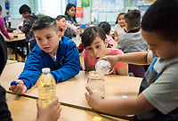 Alice Feng '20 and Alexandra Pfleegor '20 (glasses) present. Second graders Dominic Saavedra (left) and Nirvana Ramirez watch fellow students pour different liquids into jars as part of a Boundless Brilliance demonstration.<br /> Occidental students give presentations on STEM (science, technology, engineering, and mathematics) to students at Buchanan Street Elementary School in the Highland Park area of Los Angeles, Calif., March 8, 2018.<br /> In 30-minute presentations to kindergarten to sixth-grade students, Boundless Brilliance's teams of college students, all women currently attending Occidental, go into classrooms to create excitement about science. Through simple experiments (such as building a bridge between two chairs using only newspapers and tape) and a message couched in confidence, respect, and teamwork, their message to everyone—and young girls in particular—is simple: You are brilliant and you can be a scientist if you want to be.<br /> (Photo by Marc Campos, Occidental College Photographer)