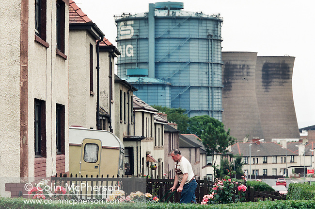 'Demolition Day, 2014'  from the project 'The Fall and Rise of Ravenscraig' by photographer Colin McPherson.<br /> <br /> Image shows a man in his garden on the day of the demolition of the former Ravenscraig steelworks in July 1996.<br /> <br /> This project, photographed in 2014, looks at the topography of the post-industrial landscape at Ravenscraig, the site until its closure in 1992 of the largest hot strip steel mill in western Europe. In its current state, Ravenscraig is one of the largest derelict sites in Europe measuring over 1,125 acres (4.55 km2) in size, an area equivalent to 700 football pitches or twice the size of Monaco. It is currently being developed with a mix of housing, retail and the home of South Lanarkshire College and the Ravenscraig Regional Sports Facility.