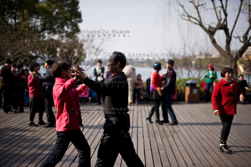 Alcune coppie ballano sul lungo lago approfittando di una giornata di sole.<br /> People dancing in a terrace in the center of Hangzhou
