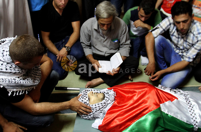 Palestinian relatives of the body of Zakariah al-Aqrah, 21, mourn during his funeral in the West Bank village of Qabalan near Nablus, Monday, Aug. 11, 2014. Al-Aqra was killed Monday in a shootout with Israeli forces after resisting arrest and holing up in a building in a village south of Nablus, local media reported. Photo by Nedal Eshtayah