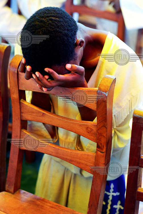 photo: Sven Torfinn .Benin, Cotonou, 2002.girl in church gown, dress, leaning on a chair, covering her face with her hands, praying in the 'eglise celeste' (celestial church), where they practise an kind of Christianity that has adopted African elements, tradition, culture, they for instance tolerate polygamy..sect, religion, belief.