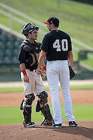 Kannapolis Intimidators catcher Brett Austin (20) has a chat on the mound with starting pitcher Zach Thompson (40) during the game against the Hagerstown Suns at CMC-Northeast Stadium on August 16, 2015 in Kannapolis, North Carolina.  The Suns defeated the Intimidators 7-2 in game one of a double-header.  (Brian Westerholt/Four Seam Images)