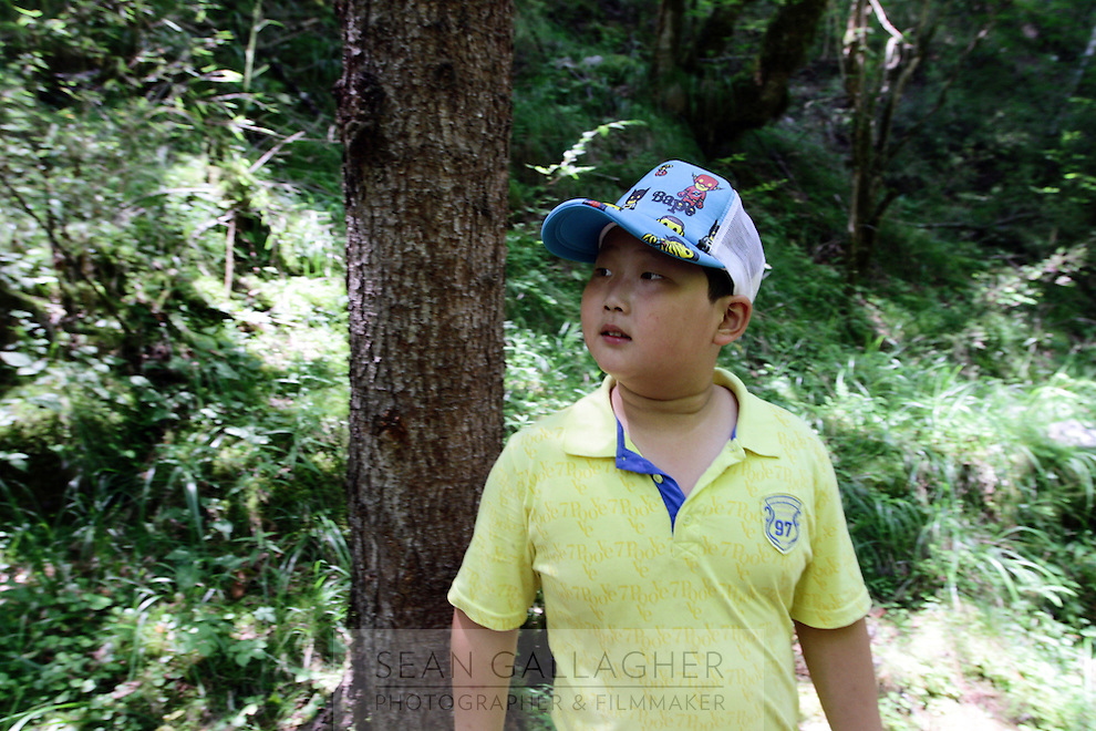 A young boy visiting the Jiuzhaigou National Park. Sichuan Province. China.
