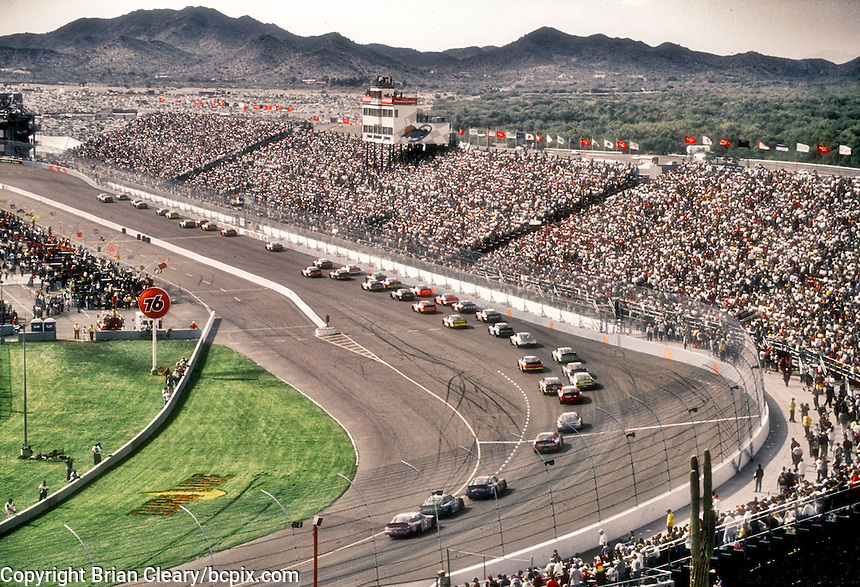 The field races down the frontstretch during the Checker Auto Parts/Duralube 500K at Phoenix International Raceway in November 2000. (Photo by Brian Cleary/www.bcpix.com)