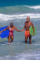 An attractive, fit senior couple holding hands stand in the surf carrying their body boards.