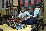 Chankuth and Nyabuay Ruot use a computer to do their homework in their family's apartment in Cairo, Egypt. The girls, whose families are refugees from South Sudan, attend classes provided by St. Andrew's Refugee Services, which is supported by Church World Service.