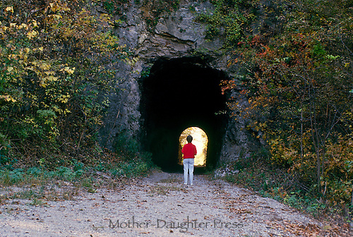 Middle aged woman stands at the entrance to a tunnel in a cliff along a walking trail, a journey. Missouri USA