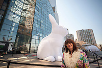 """The artist Amanda Parer in front of one of her seven giant inflatable rabbit sculptures entitled """"Intrude""""  on display in Brookfield Place in Lower Manhattan in New York on Sunday, April 17, 2016. Organized by Arts Brookfield the nylon monumental sculpture displays the humor of over-sized bunnies revealing the more serious side of an environmental problem as rabbits are an invasive species in Australia. The exhibit will be on view until April 30 when it goes on tour to Houston and Los Angeles. (© Richard B. Levine)"""