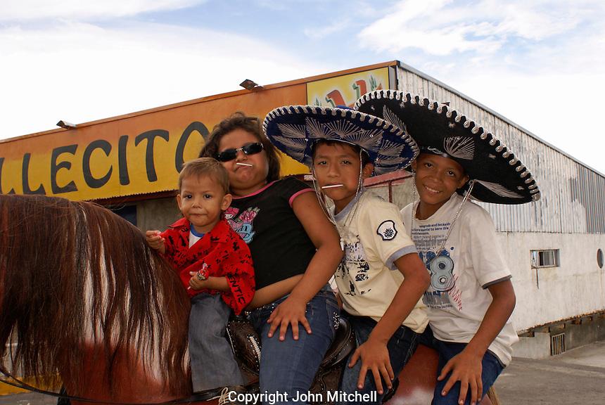 Nicaraguan children sitting on a model horse, Managua, Nicaragua