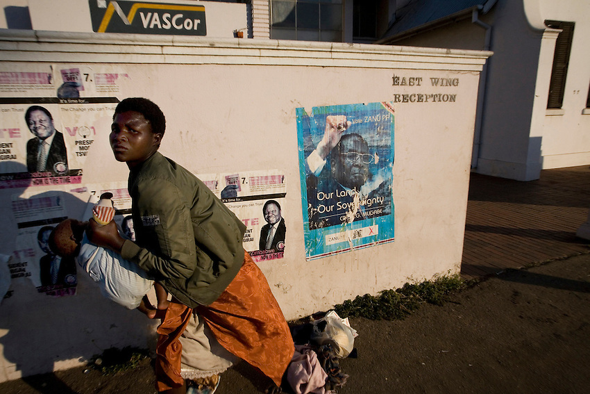 A woman carries her child passed posters of Robert Mugabe and Morgan Tsvangirai in downtown Harare, Zimbabwe, Thursday, July 3, 2008.