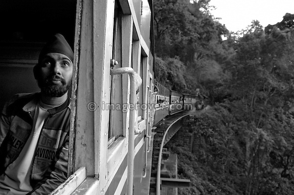 Indian man travelling in the Nilgiri Mountain Railway. Looking out of the window while the steam train is crossing one of the many bridges between Coonoor and Metapulayam. Part of the journey is managed only by a rack-and-pinion system. India, Tamil Nadu 2005. --- Info: The Nilgiri Mountain Railway (NMR) is the only rack railway in India and connects the town of Mettupalayam with the hill station of Udagamandalam (Ooty), in the Nilgiri Hills of southern India. The construction of the 46km long meter-gauge singletrack railway in Tamil Nadu State was first proposed in 1854, but due to the difficulty of the mountainous location, the work only started in 1891 and was completed in 1908. This railway, scaling an elevation of 326m to 2,203m and still in use today, represented the latest technology of the time. In July, UNESCO added the NMR as an extension to the World Heritage Site of Darjeeling Himalayan Railway.