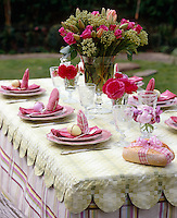 Detail of a table laid for a spring lunch in the garden with a scalloped green and white runner over a tartan tablecloth