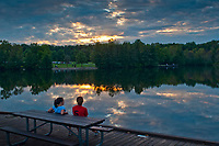 Two women sit at sunset at Schrock lake at Sharon Woods Metro Park in Columbus, Ohio. The sunset is reflected in the  smooth water of the small lake used for fishing by park goers.