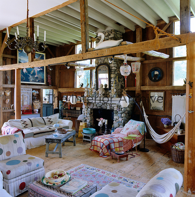 The open-plan living area of the barn is filled with objects of sentimental value and furnished with an assortment of chairs and sofas, some hand-painted with colourful polka dots