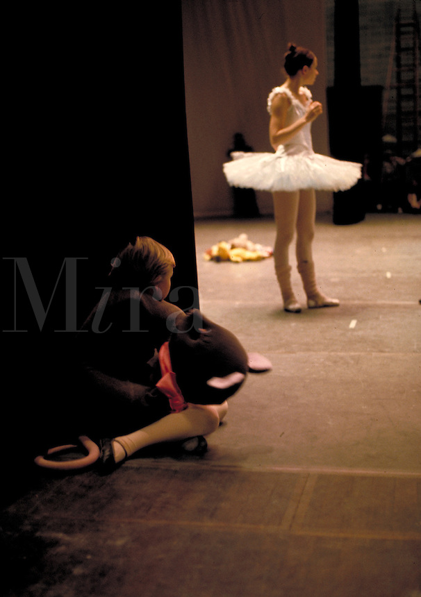 Young ballerina in a mouse costume watches the lead dancer and waits her turn during a dance rehearsal , dancers, dancing, ballet recital.