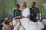 Brother Antonio Nunes Ferreira, a Comboni missionary nurse who teaches at the Catholic Health Training Institute (CHTI) in Wau, South Sudan, talks with a patient in the St. Daniel Comboni Catholic Hospital in Wau as two CHTI nursing students look on. <br /> <br /> Nunes is a member of Solidarity with South Sudan, an international network of Catholic groups training teachers, medical personnel, and pastoral workers in the world's newest country. Solidarity sponsors CHTI.