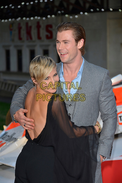 Elsa Pataky and Chris Hemsworth<br /> 'Rush' world film premiere at the Odeon Leicester Square cinema, London, England.<br /> 2nd September 2013<br /> half length suit grey gray black  sheer married husband wife  jumpsuit waistcoat  backless arm around waist looking over shoulder <br /> CAP/PL<br /> &copy;Phil Loftus/Capital Pictures