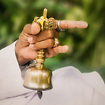 A Balinese priest's hand, chiming a bell during prayer, represents HARMONY BETWEEN HUMANS AND GOD, one of the Balinese principals of Tri Hita Karana that guided development of a new heling center.