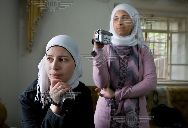 Video volunteers Sunduz and Shatha Alhaddad use a video camera, given to her by Israeli human rights group B'Tselem, to record the abuse that her family faces from Israeli settlers living opposite their house...