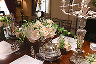 Elegant flowers and silver pieces on a wedding reception buffet.