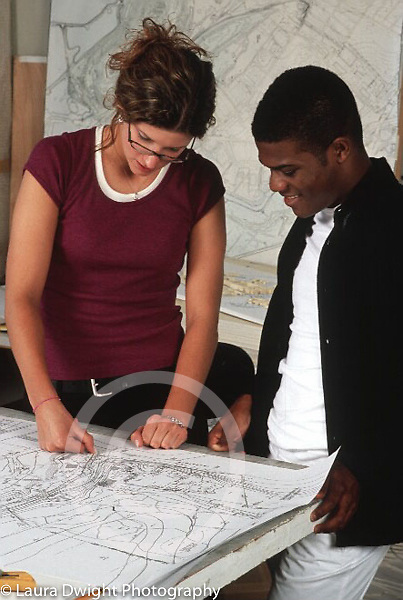 Internship program for college students at major architectural firm, two students working on plans