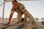 At a border crossing point in Iraq a British Army engineer searches bags of cement on the back of a truck from Iran. Iran were accused of supplying arms and bomb making equipment to Iraqi terrorists.