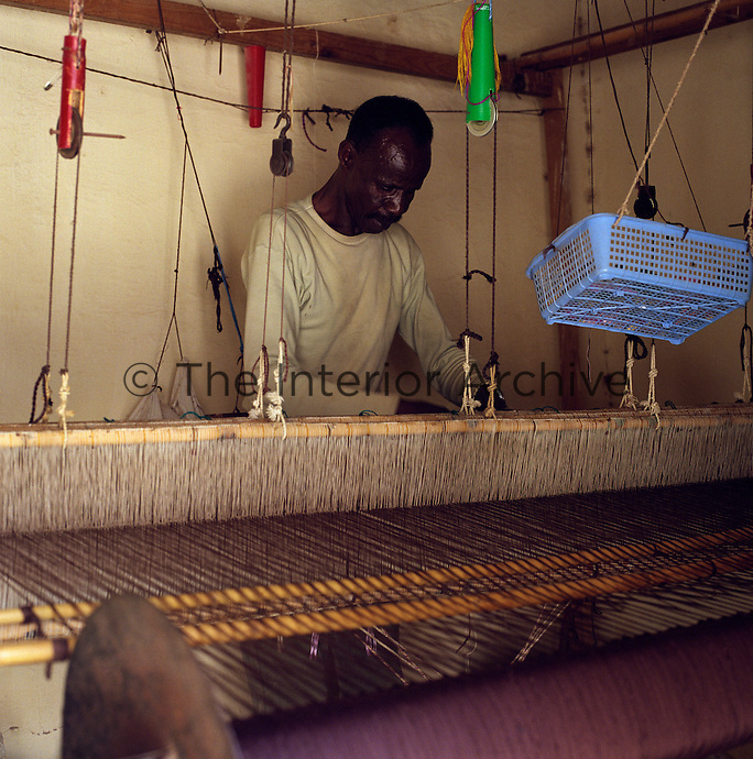 A man works at his loom weaving richly coloured textiles which are typical of the region