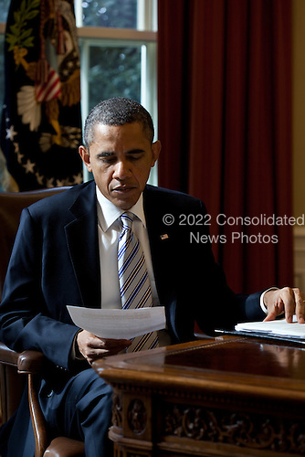 United States President Barack Obama reads a document in the Oval Office, February 21, 2012.  .Mandatory Credit: Pete Souza - White House via CNP