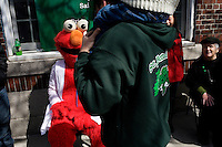 A person dressed as Elmo from Sesame Street watches the St. Patrick's Day Parade in South Boston, Massachusetts.