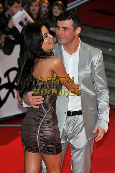JOE CALZAGHE & GUEST .Arrivals - 2009 Brit Awards, Earls Court, London, England, February 18th 2009..half length brown one shoulder ruffle ruched dress suit shiny white shirt silver .CAP/PL.©PL/Capital Pictures