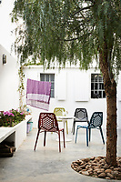 A simple plastic table and four chairs are set out on a patio terrace.