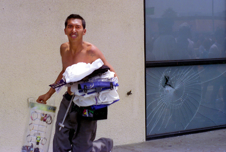 "A man runs with clothing still on store hangers during the ""uprising"" of rioting and looting in the Koreatown neighborhood of Los Angeles, Calif. following the acquittal of LAPD officers accused of beating motorist Rodney King, May 30, 1992. Photo copyright Gerard Burkhart 818-207-0273)during the ""uprising"" of rioting and looting in the Koreatown neighborhood of Los Angeles, Calif. following the acquittal of LAPD officers accused of beating motorist Rodney King, May 30, 1992. Los Angeles suffered city wide chaos and destruction following the the end of the first trial against accused officers Sergeant Stacey Koon, Laurance Powell, Theodore Briseno and Timothy Wind. A later  Federal Civil Rights Trial sent officers Powell and Koon to prison for 30 months while Briseno and Wind were acquitted. Photo copyright Gerard Burkhart 818-207-0273)"