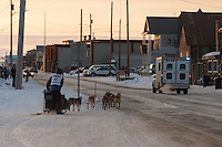 Becca Moore runs on Front Street with a police escort just a mile from the finish line in Nome on Saturday March 21, 2015 during Iditarod 2015.  <br /> <br /> (C) Jeff Schultz/SchultzPhoto.com - ALL RIGHTS RESERVED<br />  DUPLICATION  PROHIBITED  WITHOUT  PERMISSION